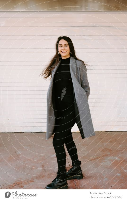 Happy young woman spinning around on street city smile urban style fun dance female excited coat trendy building wall fashion happy amazed model lady cheerful