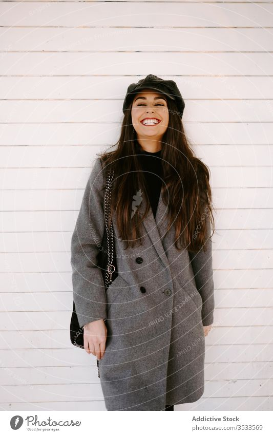 Confident young female near white wall woman style street confident cap building coat outfit model urban wear accessory hat brunette headgear exterior lady