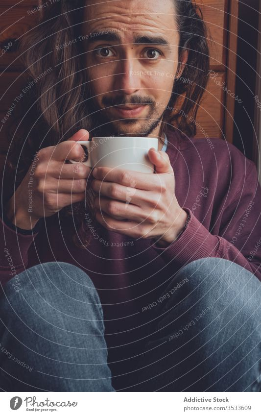 Bearded man resting with hot beverage drink home coronavirus stay at home covid-19 cozy mug mood adult room male relax tea coffee cup comfort long hair beard