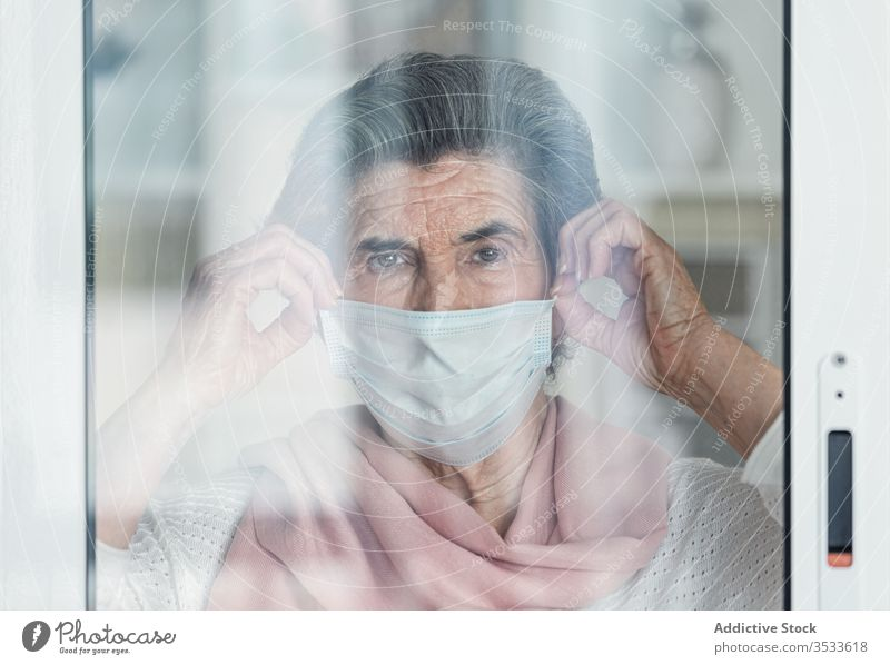 Lonely senior female looking out window woman lonely medical mask epidemic home elderly coronavirus risk group touch glass patient aged care sick retire