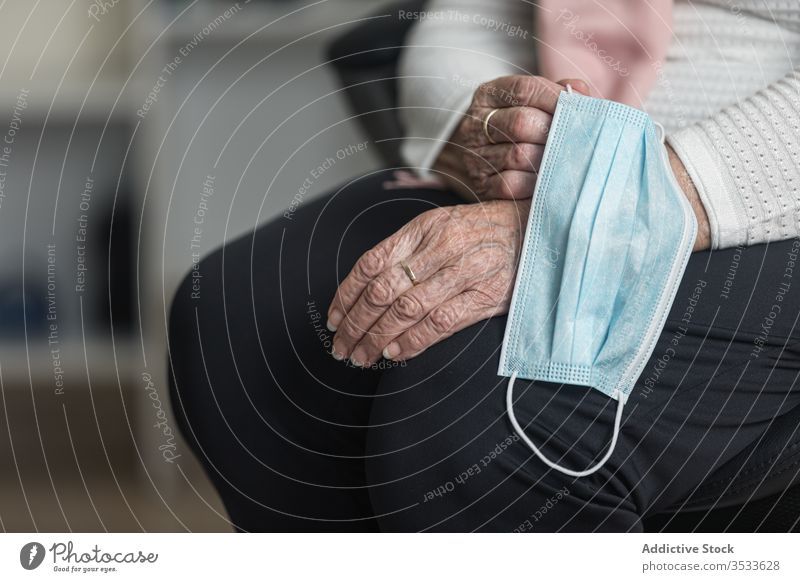 Crop senior woman with medical mask at home epidemic elderly chair sit coronavirus risk group female patient wrinkle aged care sick retire pandemic covid 19