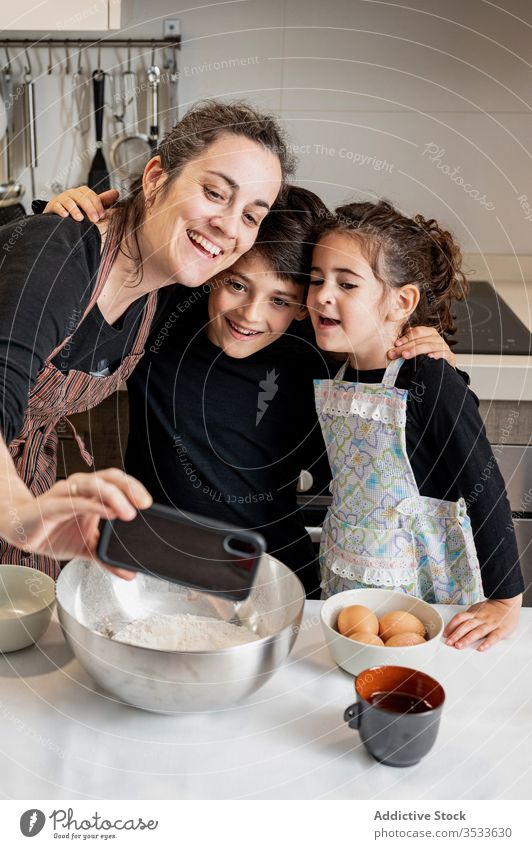 Mother taking selfie with kids during pastry preparation mother children cook home kitchen smartphone mobile phone smile happy love together cozy girl boy woman