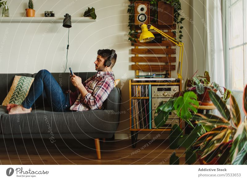 Man listening to music and using smartphone on couch man sofa home comfort weekend rest male browsing headphones lounge lifestyle surfing living room sound