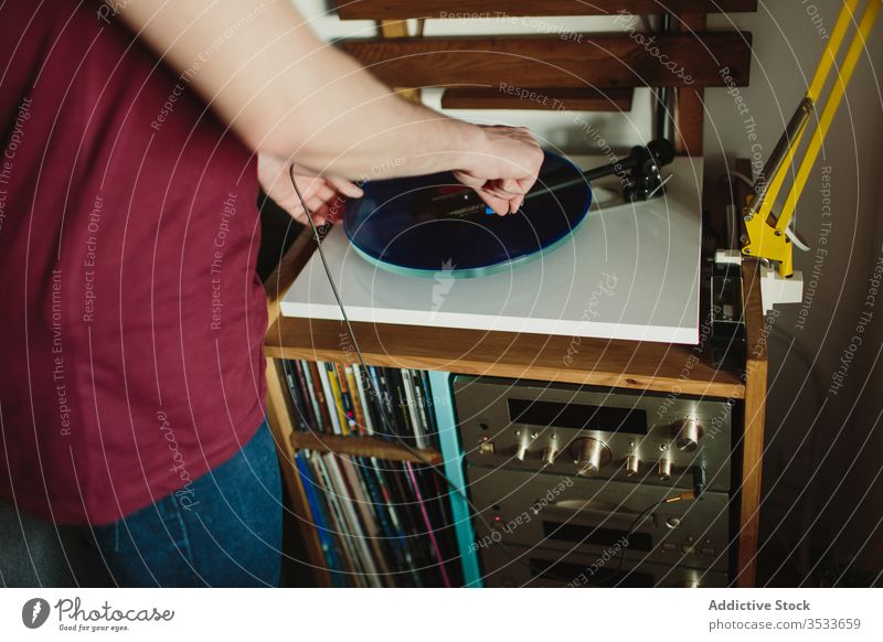 Anonymous person putting disc on record player man music listen home vinyl cozy weekend hobby male turntable casual room headphones retro vintage audio stereo