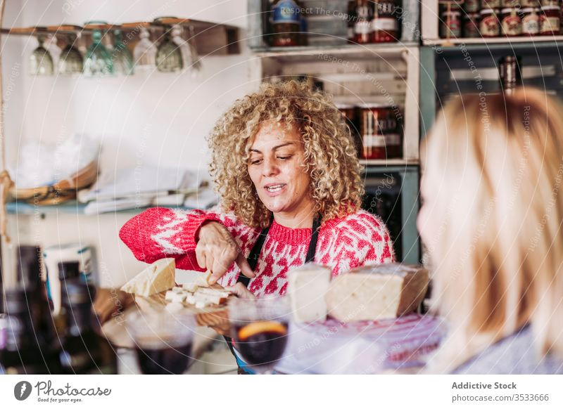Cheerful seller communicating with client speak product happy work service grocery copy space hair curly talk employee friendly smile store dairy shop purchase