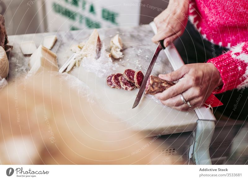 Crop seller cutting sausage on counter shop food local cuisine work knife cheese meal yummy market tasty product tradition gourmet delicious fresh store grocery