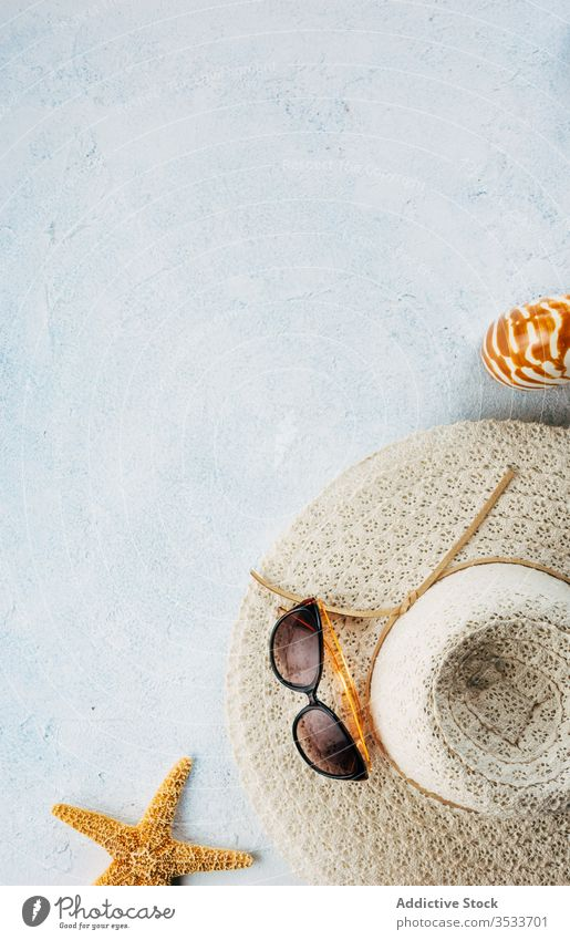 Sunglasses and hat on stucco surface near seashells sunglasses summer vacation style accessory beach composition trendy fashion plaster travel tourism trip