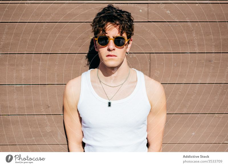 Stylish man standing near wall street modern style urban young city sunglasses tank top male trendy model hipster sunny building construction cool summer town