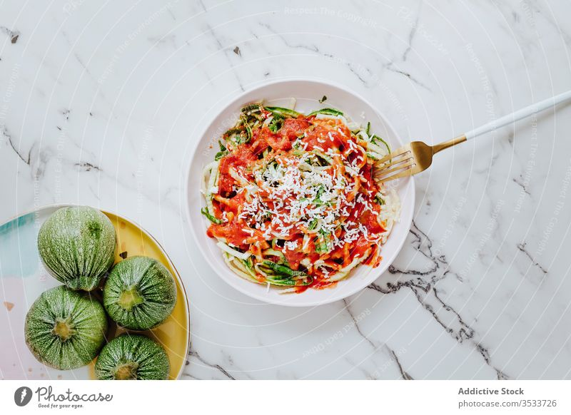 Homemade zucchini noodles with cheese and tomato sauce pasta healthy food veggie natural mix green culinary fork meal plate red lunch breakfast bowl dishware