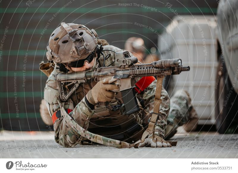 Soldier aiming airsoft gun during tactical game man soldier shoot camouflage ground lying male uniform military adult protect match weapon equipment