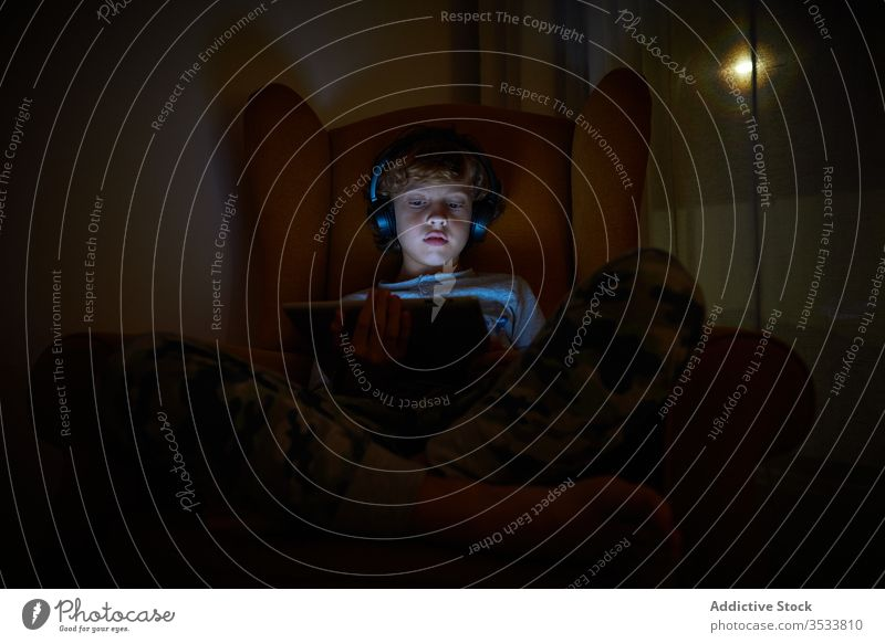 Child sitting in an armchair in a corner of a room with a tablet on his lap with headphones at night boy multimedia communication listen game play device draw
