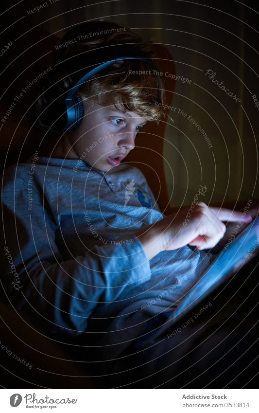 Vertical photo of a child sitting with headphones on a sofa touching the screen of a tablet at night boy pointing interact imagination cinema lateral multimedia