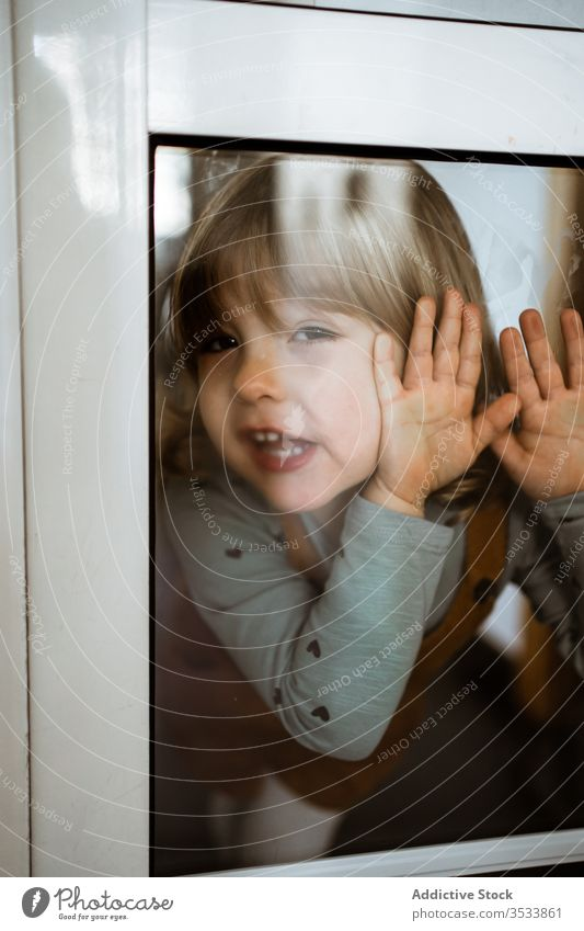 Happy little girl behind window happy home smile casual cute touch glass kid child cheerful childhood room playful curious rest lifestyle relax innocent cozy
