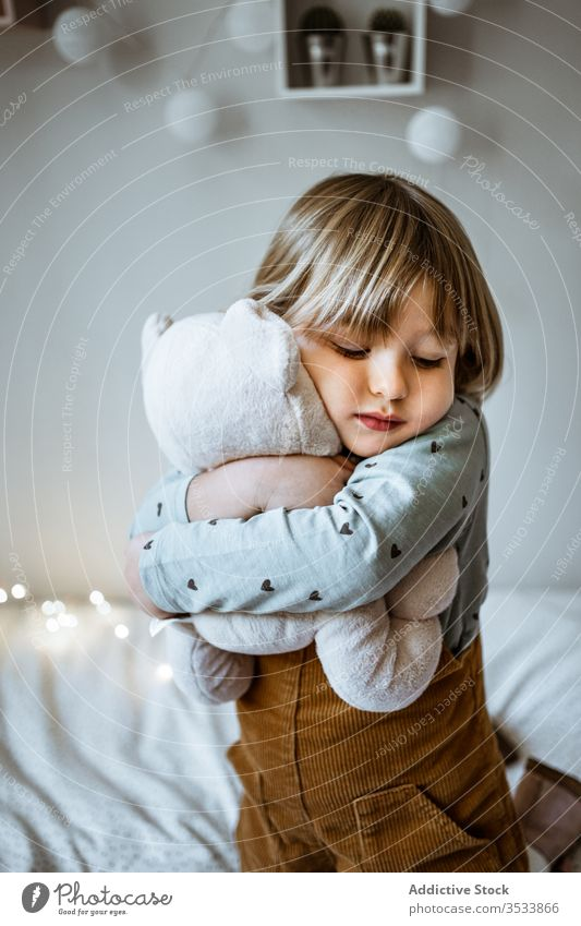 Happy girl playing on soft bed happy toy hug laugh fairy light plush lying excited child kid love garland bedroom little childhood lifestyle leisure fun cute