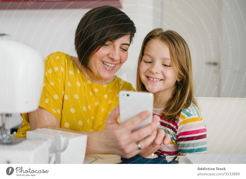 Happy seamstress taking selfie with daughter mother smartphone workshop tailor smile home together woman girl table cheerful adult child happy dressmaker