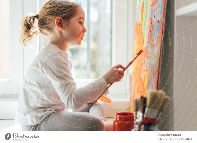 Little girl painting picture with paintbrush canvas draw rainbow creative colorful orange sill casual window art hobby imagination bright sit indoors