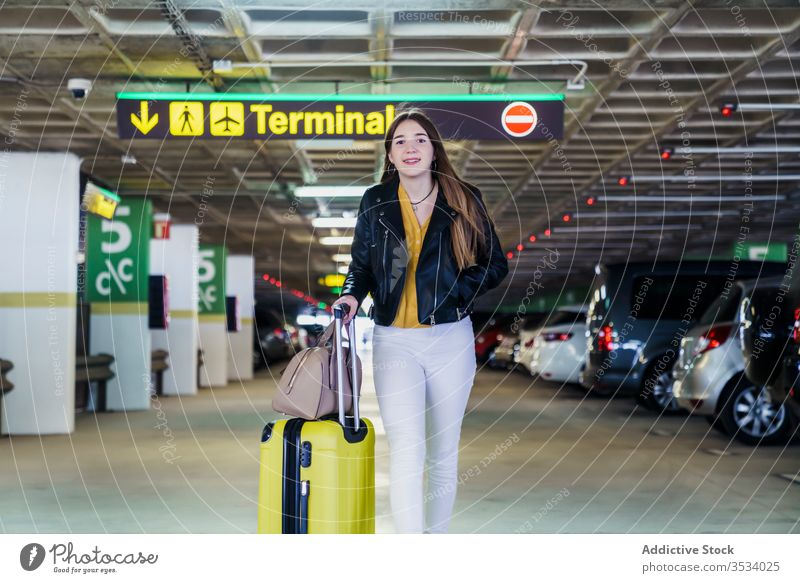 Trendy female passenger walking along airport parking woman traveler suitcase carry joy luggage smile bag trip flight wait journey tourist arrive terminal
