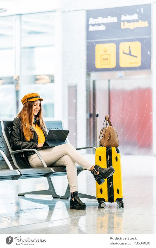 Woman using laptop on in waiting area of airport woman tablet flight delay browsing passenger luggage style departure colorful surfing yellow bench trendy