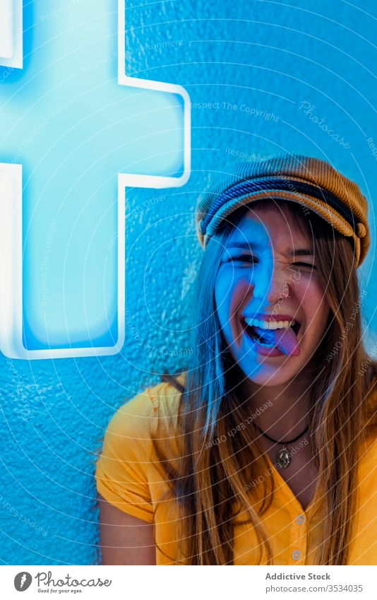 Young cheerful woman making funny face on blue background show tongue neon rebel tongue out make face having fun grimace sign yellow trendy wall medical cross