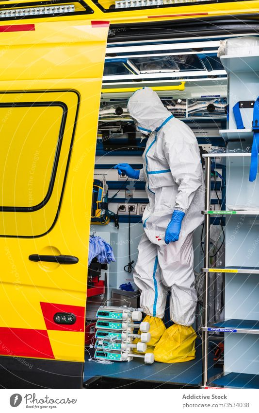 Doctor in protective suit standing in ambulance car doctor door equipment patient virus infection examine uniform inspect hospital service vehicle safety