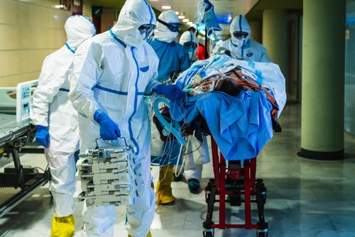 Group of doctors transporting patient to operating room group hospital viral infection hall clinic uniform mask specialist equipment health care medicine