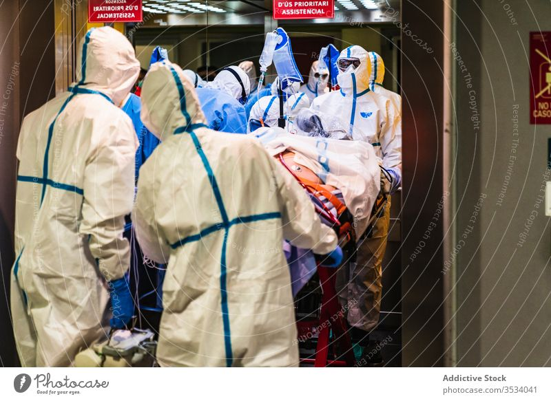 Group of doctors in protective uniform taking patient from elevator group clinic hospital health care mask job specialist equipment medicine treat staff