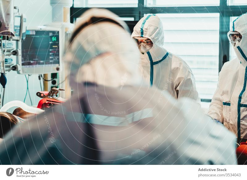 Doctors in protective uniform working in operating room in hospital doctor clinic viral patient care infection equipment treat specialist mask health care