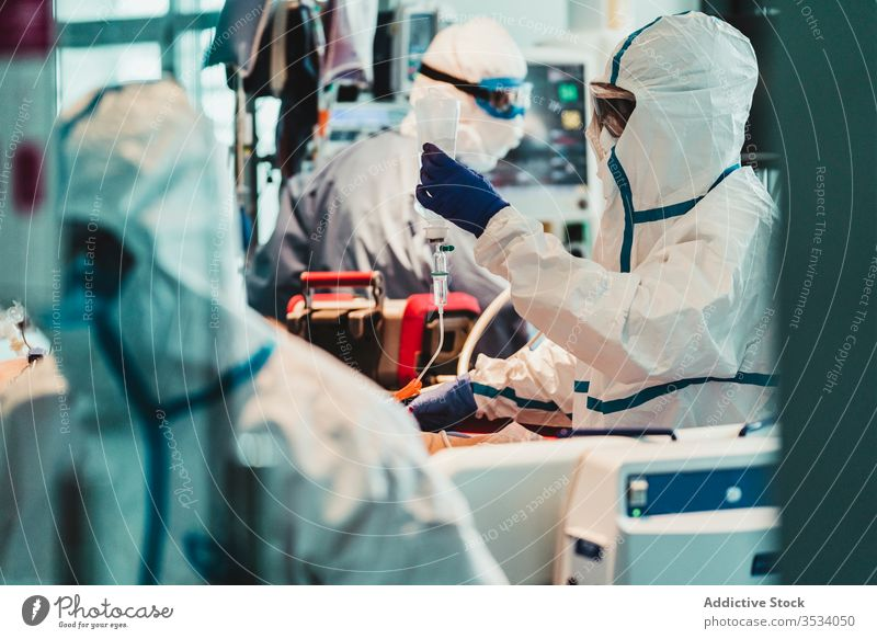 Group of professional doctors working in operating room during pandemic uniform equipment clinic glove specialist examine check occupation protect health care