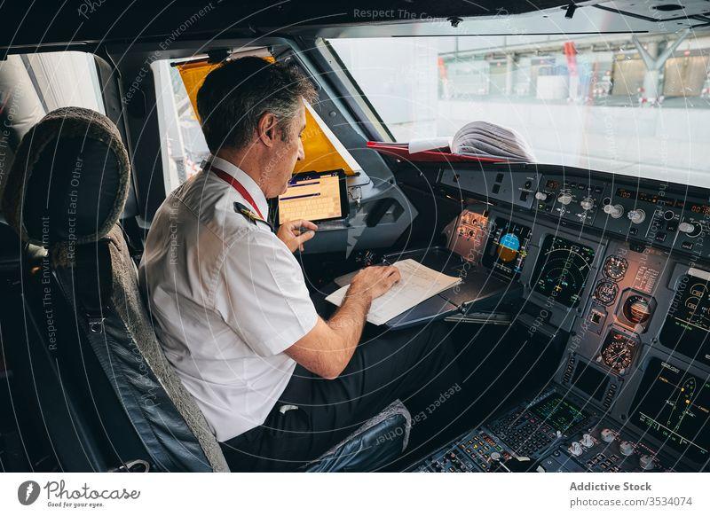 Captain checking flight document in airplane cockpit pilot read captain prepare man aviator male modern aircraft transport aviation departure work occupation