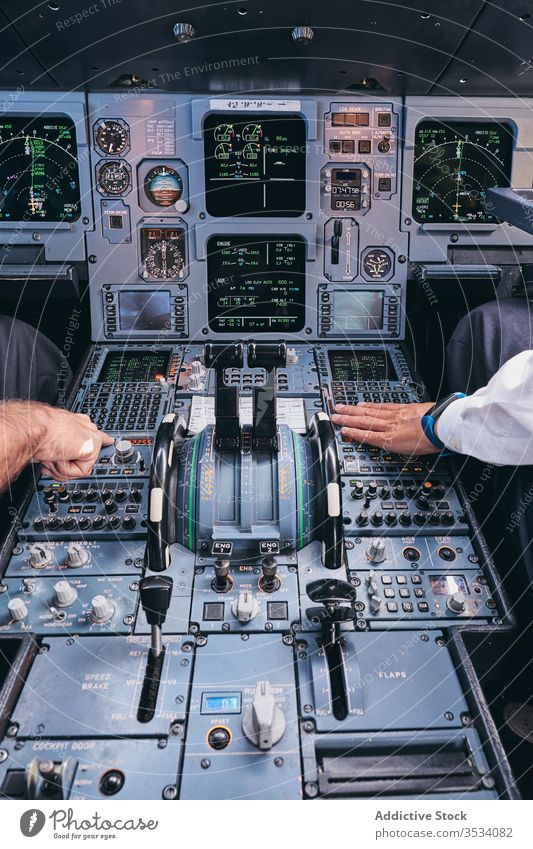 Pilots working in cockpit during flight pilot operate men airplane control dashboard equipment aviator male captain check modern aircraft transport instrument