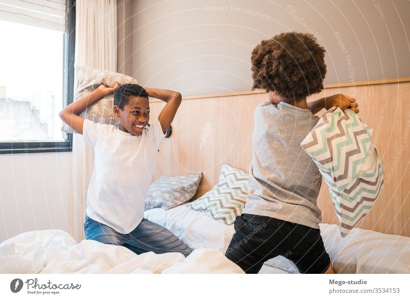 Two brothers playing with pillows at home. kids together happy bedroom excited portrait positive active pillow fight adorable lifestyle black happiness