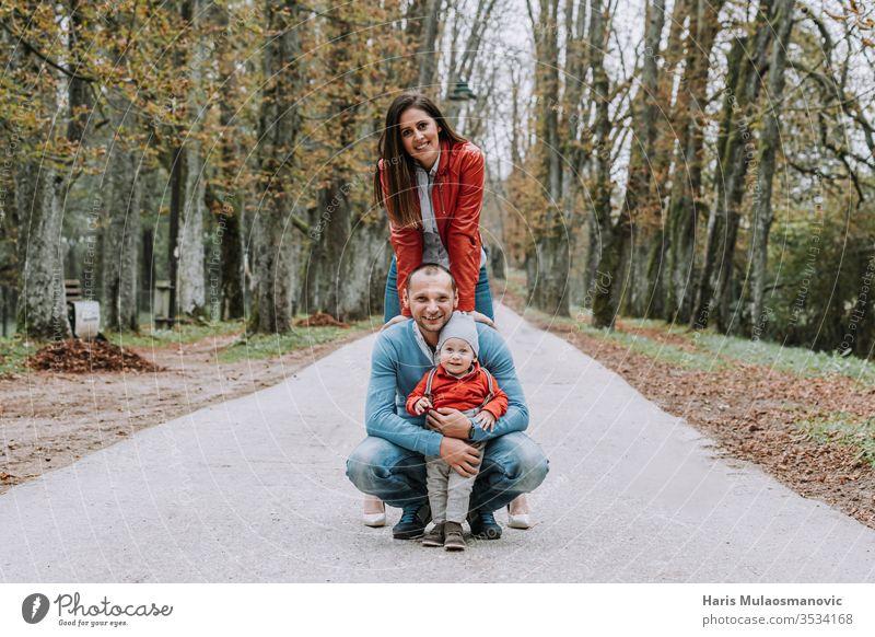 Happy family stylish couple with 1 year old child smiling in the park in red and blue clothes beautiful care caucasian cheerful childhood concept cute dad daddy