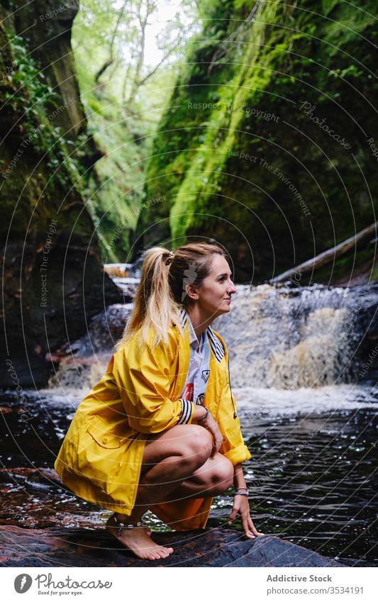 Cheerful female tourist crouching near waterfall and green mountain nature explore happy woman idyllic wanderlust paradise vacation cascade recreation harmony