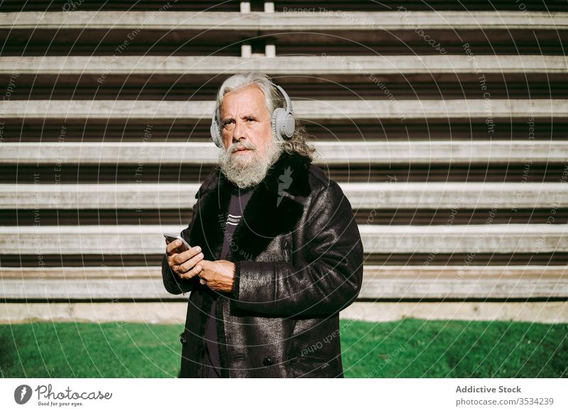 Elderly man listening to music in headphones during city stroll elderly hipster smartphone using male senior serious aged pensive modern thoughtful enjoy song