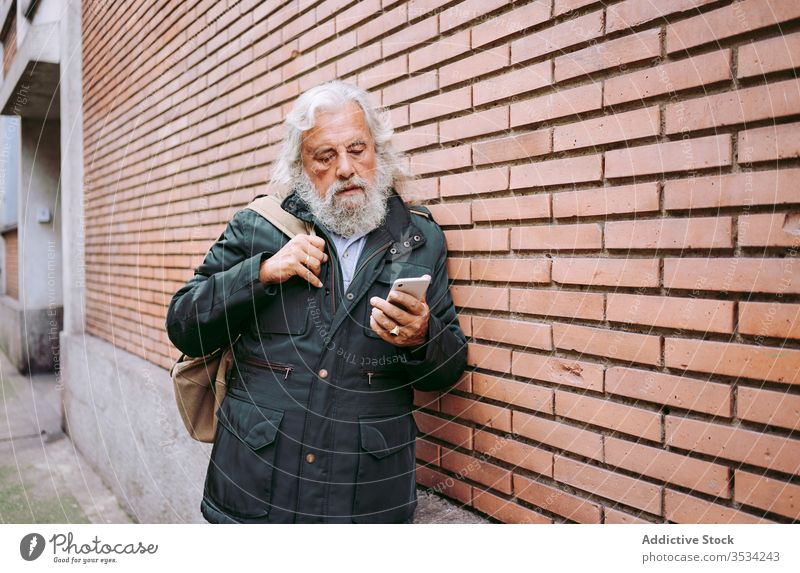 Male hipster using mobile phone on a brick wall senior man smartphone city serious street male elderly aged leaning gray hair long hair masculine handsome
