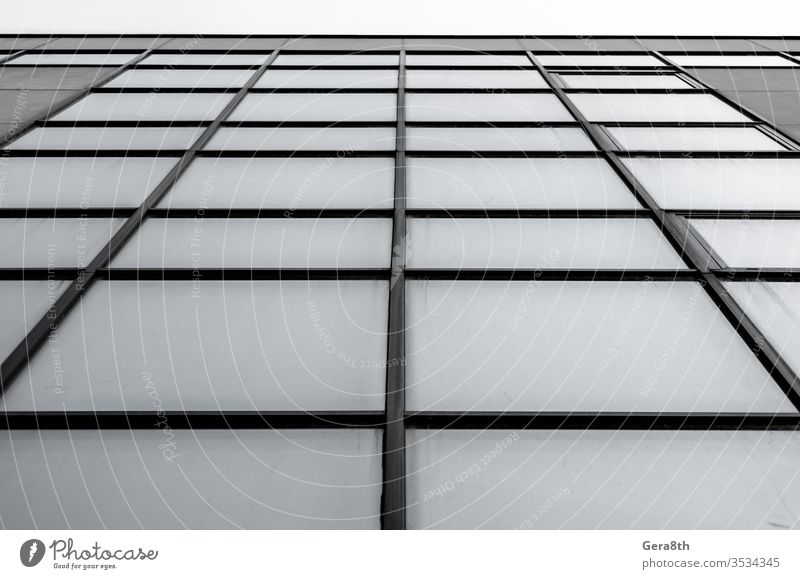 empty windows of a gray high concrete building close up abstract architecture background blocks business city fragment glass gloomy house lines minimal modern