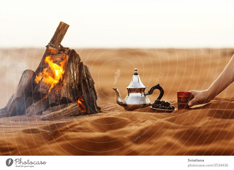 Dates, teapot, cup with tea near the fire in the desert with a beautiful background dates ramadan arabic culture coffee food kettle tradition sand turkish sun