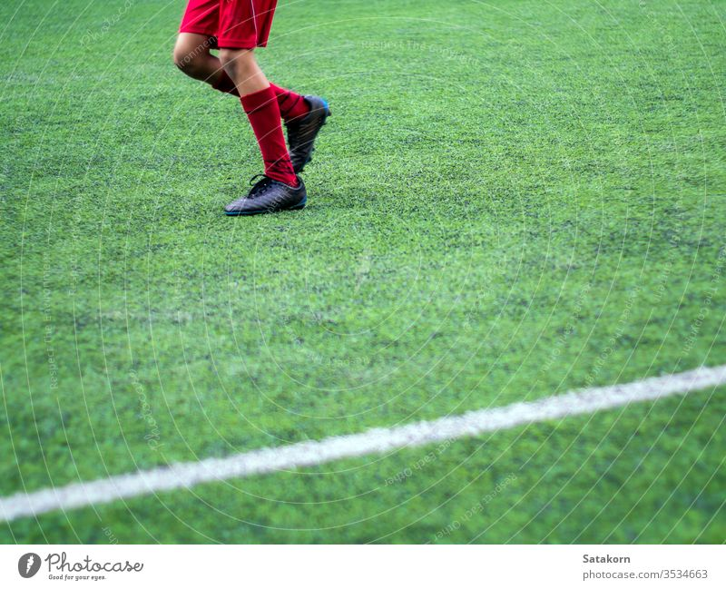 The footballers are competing in color sports of elementary school soccer children kids game green match play boy young background field player training grass
