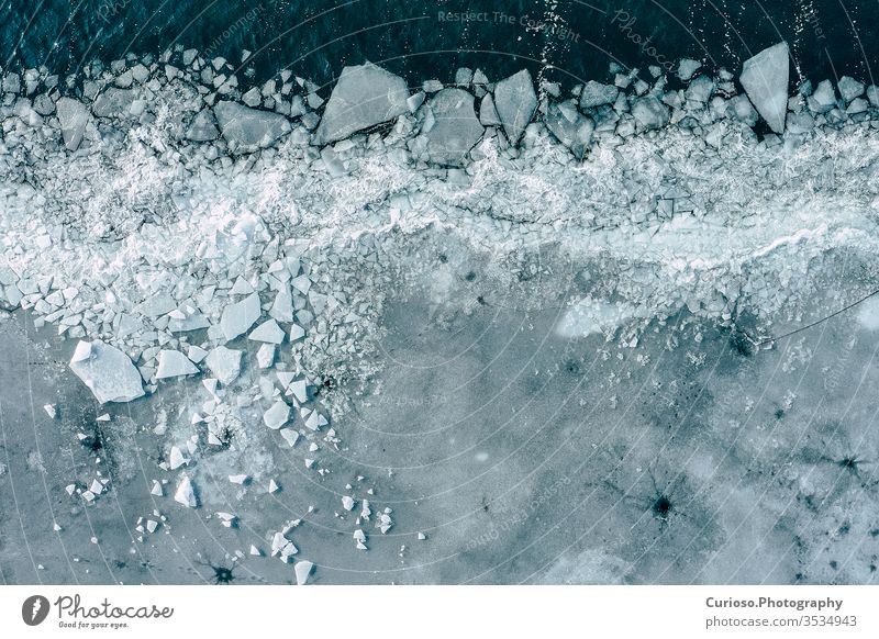 Glacier Lagoon with icebergs from above. Aerial View. Cracked Ice from drone view. Background texture concept. blue glacier water white nature landscape arctic