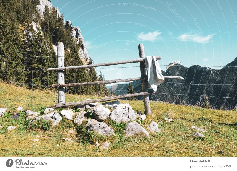 Slate wooden fence in the mountains serves as a barrier and towel rail Alps Mountain Sky Blue Rock Peak Landscape Nature Exterior shot Colour photo Day