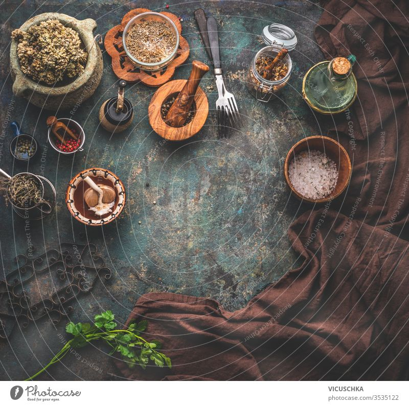 Rustic background with vintage kitchen utensils. Herbs and spices in wooden bowls, olives oil and napkin. Frame. Top view. rustic food background herbs frame