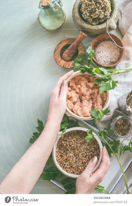 Woman hands holding bowls with ingredients für tasty cooking. Top view female preparation light kitchen tables fresh seasoning woman top view people lifestyle