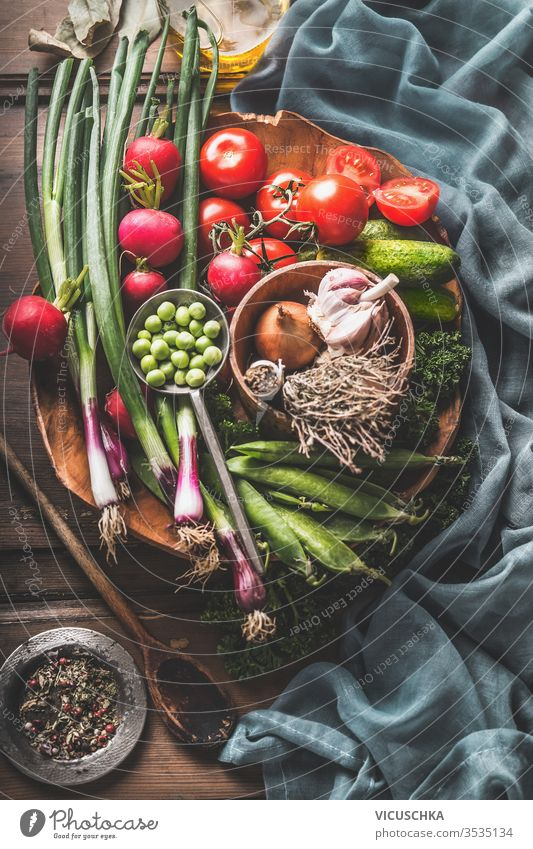 Vegetarian cooking ingredients with various organic vegetables from garden and wooden cooking spoon. Healthy food. Home cuisine. Paleo diet. weight loss eating