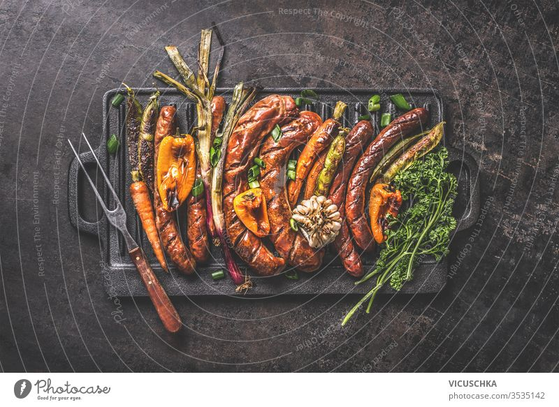 Various grilled meat sausages with roasted vegetables on cast iron grill pan with meat fork on dark rustic background. Grill party Oktoberfest German food. Top view. Traditional cuisine
