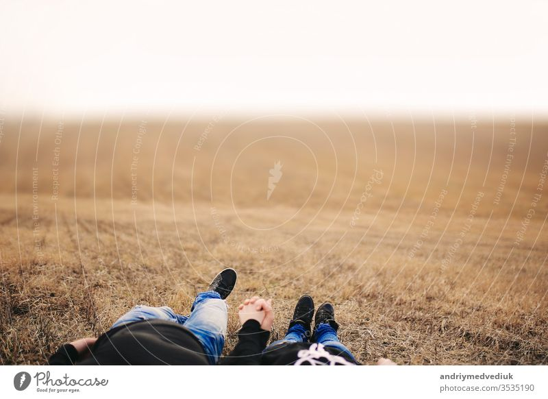 Couple in love man and woman lying in field holding hands. Concept of love. Autumn mood. Place for inscription people summer two together happy adult attractive