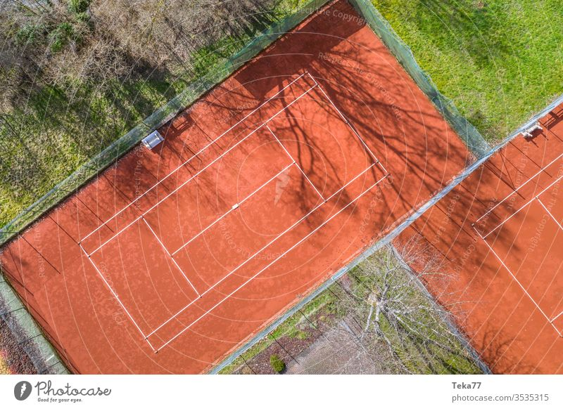 a tennis court from above sport sports tennis courts ash orange white lines sun shadow summer winter sharp tennis net tennis nets ball balls tennis ball trees