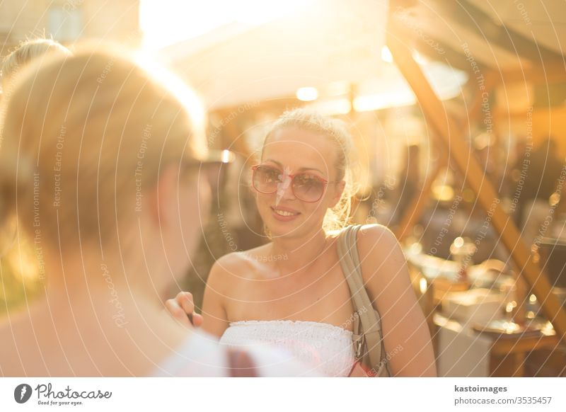 It is nice to see you. It has been a while. Two happy young female friends enjoying a conversation on urban food market at random after work encounter. Pleasant free time socializing