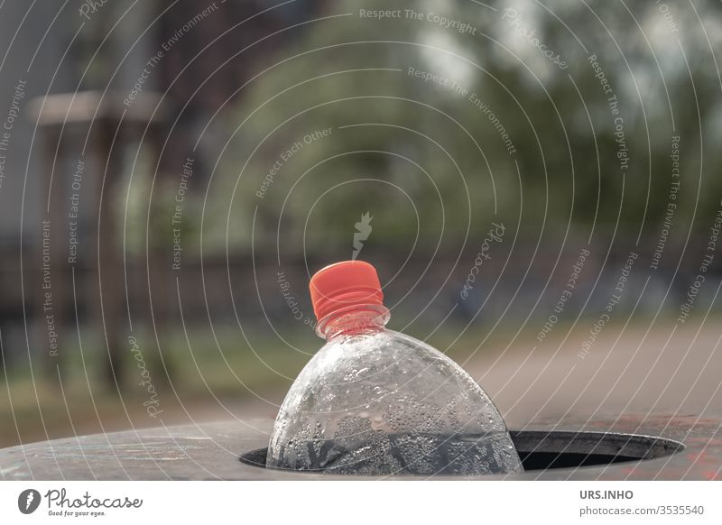 an empty PET bottle with an orange screw cap is disposed of in the waste basket Polyethylene terephthalate pet Neck of a bottle Wastepaper basket Throw away