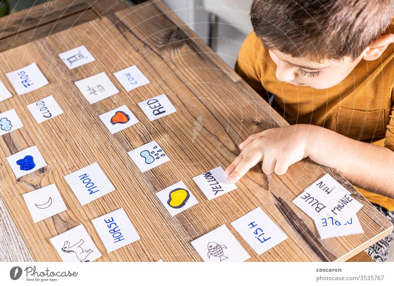 Little kid playing with cards of words and pictures. alphabet back to school boy cartoon childhood children classroom concentrate coronavirus education