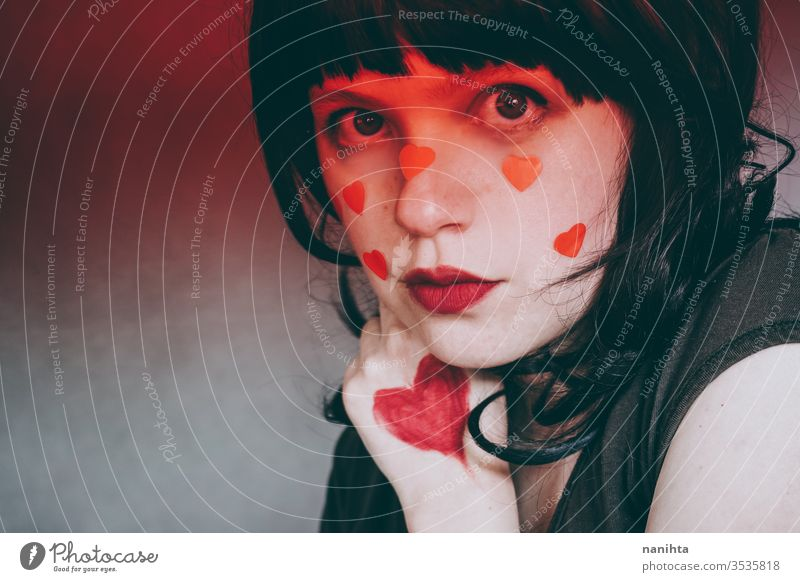 Artistic portrait of a young woman with red heart make up and covering by a red gradient ligth love beauty pretty face artistic valentines valentine's day